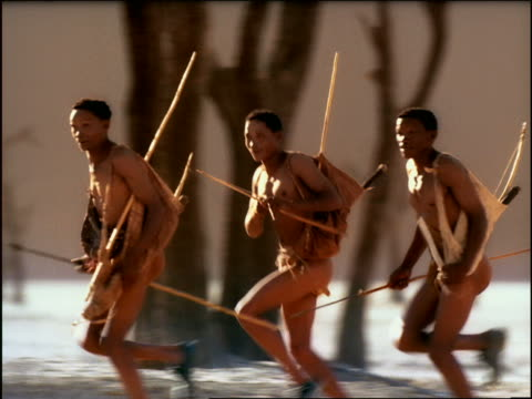 overexposed tracking shot three bushmen carrying spears running in desert / namibia, africa - overexposed stock videos & royalty-free footage