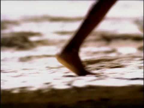 vídeos de stock e filmes b-roll de overexposed tracking shot three bushmen's legs running in desert (carrying spears) / namibia, africa - super exposto