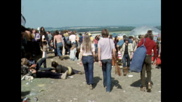 vídeos de stock e filmes b-roll de tracking shot through crowds of festival goers; 1970 - jeans
