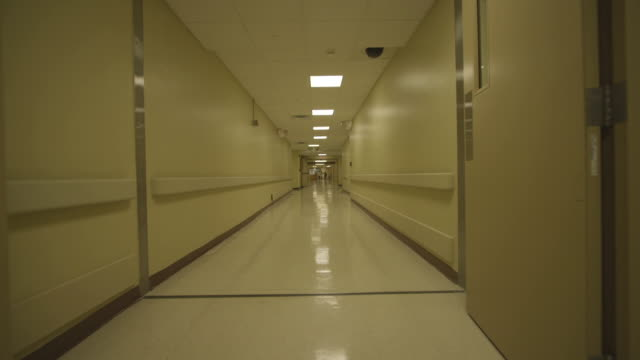 tracking shot through hospital hallway - krankenhaus stock-videos und b-roll-filmmaterial