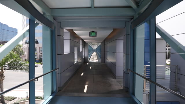 tracking shot through modern hospital hallway/skyway - corridor stock videos & royalty-free footage