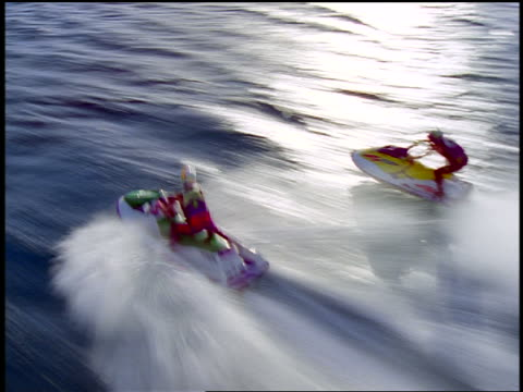 aerial tracking shot time lapse two people in helmets riding jet boats speeding across water surface in race - acquascooter video stock e b–roll