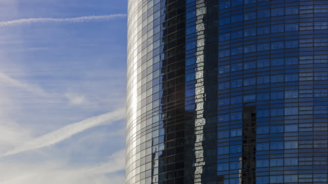 tracking shot tl of moving reflections in building and moving clouds in financial district - curtain wall facade stock videos and b-roll footage