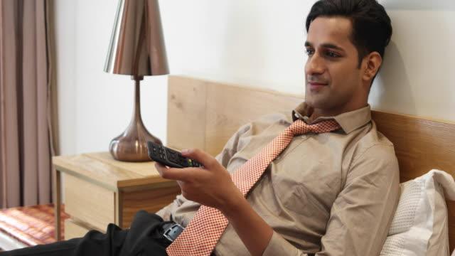 vídeos y material grabado en eventos de stock de tracking shot to a man watching television after work at home - corbata