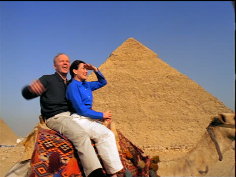 tracking shot tourist couple riding camel pointing, shielding eyes + kissing past Great Pyramids / Giza, Egypt