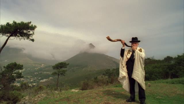 Tracking shot towards a Jewish man blowing a shofar atop a mountain