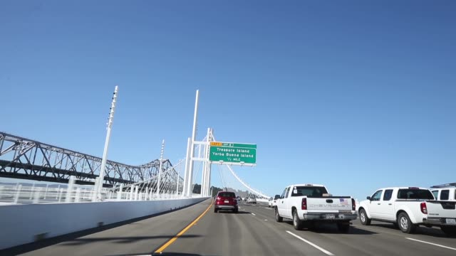 vídeos de stock e filmes b-roll de tracking shot, traffic flows across the new eastern span of the san francisco oakland bay bridge as the old eastern span sits empty on the morning... - san francisco oakland bay bridge