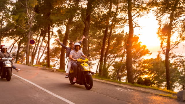 MS tracking shot two couples riding scooter on coastal road at sunset