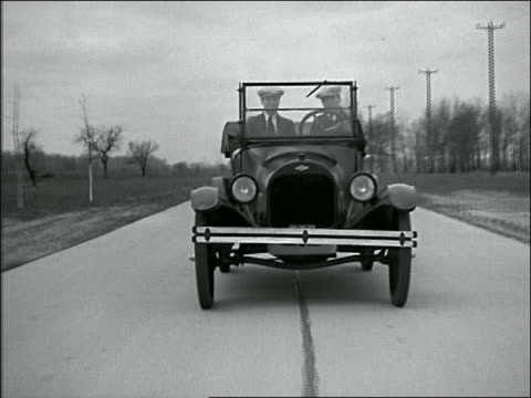 B/W 1924 REENACTMENT tracking shot two men driving convertible Chevrolet on country road