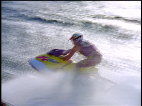 aerial tracking shot two people in helmets riding jet boats speeding across water surface in race - acquascooter video stock e b–roll