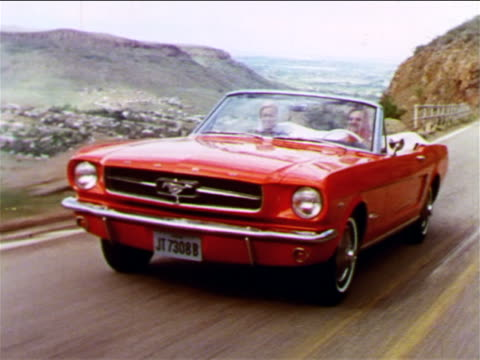 1965 tracking shot two women driving red convertible Ford Mustang on mountain road / industrial