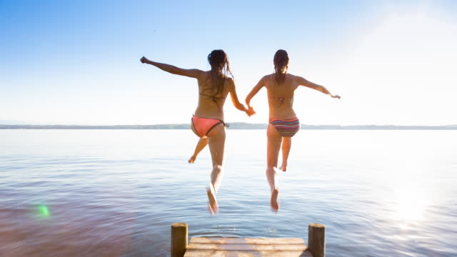 vidéos et rushes de ws tracking shot two young women enjoying the summer jumping from lakeside deck - s'amuser