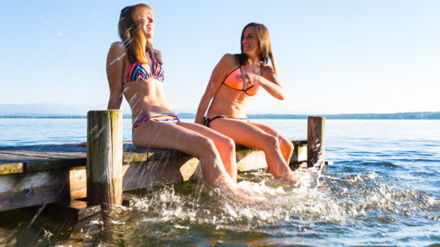 MS tracking shot two young women enjoying the summer on lakeside deck splashing water