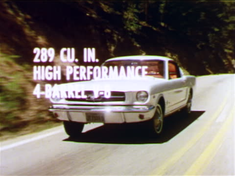 1965 tracking shot white Ford Mustang driving toward camera on country road / graphics superimposed in shot
