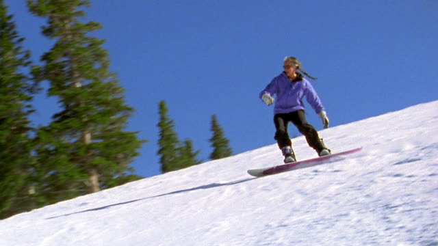 tracking shot woman snowboarding down ski slope and falling - snowboarding stock videos & royalty-free footage