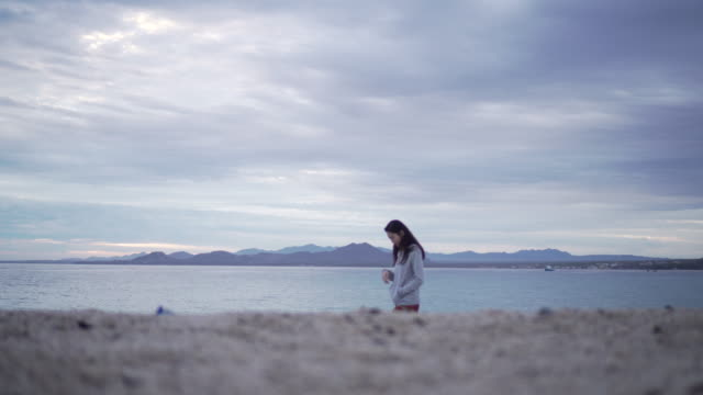 Tracking shot, woman walks alone on beach in Mexico