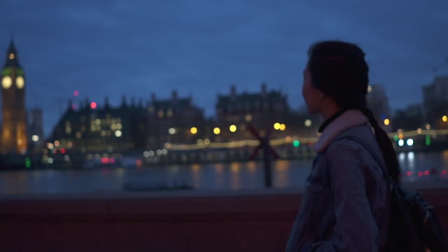 tracking shot, woman walks along thames river - big ben stock videos & royalty-free footage