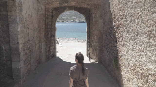 vídeos de stock e filmes b-roll de tracking shot, woman walks down alleyway to coast - greece