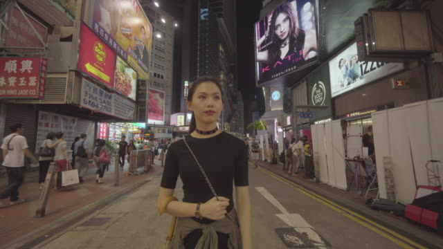 tracking shot, woman walks down street in hong kong - poster design stock videos and b-roll footage