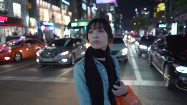 Tracking shot, woman walks downtown at night