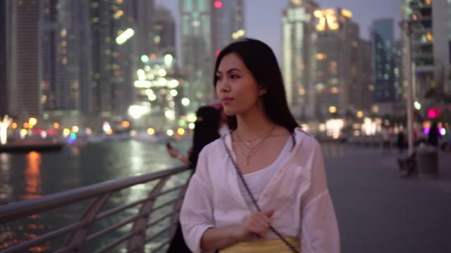 tracking shot, woman walks in dubai at night - nightlife stock videos & royalty-free footage