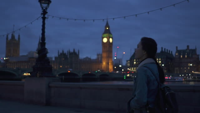 Tracking shot, woman walks in London at night