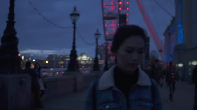 tracking shot, woman walks on bridge in london - london eye stock videos & royalty-free footage
