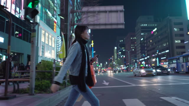 stockvideo's en b-roll-footage met tracking shot, woman walks on crosswalk at night - stadsweg