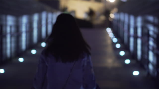 Tracking shot, woman walks on pier in Hong Kong
