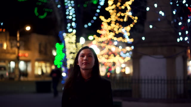 vídeos de stock e filmes b-roll de tracking shot, woman walks past holiday lights in new mexico - luzes de natal