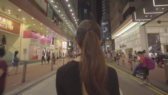 Tracking shot, woman walks past pedestrians in Hong Kong