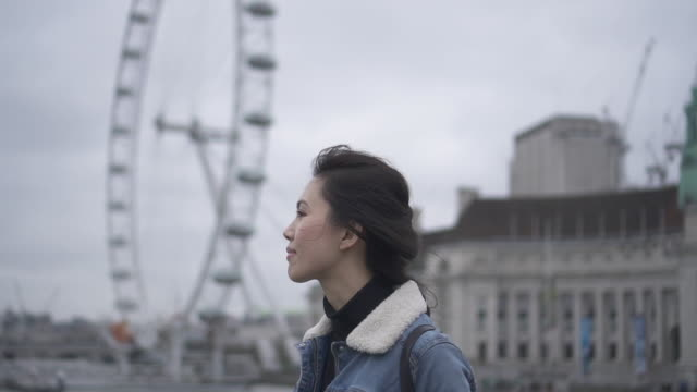 tracking shot, woman walks past the eye in london - hairstyle stock videos and b-roll footage