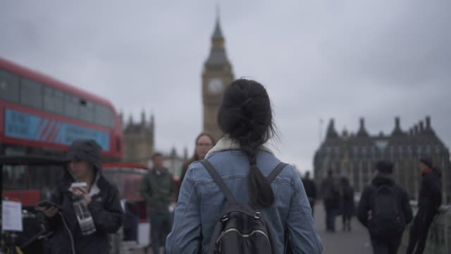 vídeos de stock e filmes b-roll de tracking shot, woman walks to big ben in london - vista traseira