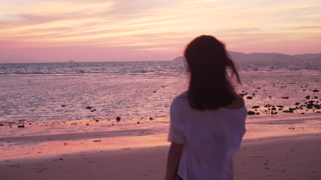 tracking shot, woman walks to ocean at sunset - solo una donna di età media video stock e b–roll