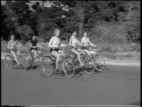 B/W 1933 tracking shot women riding on bouncing bicycles on road / San Francisco, California / newsreel