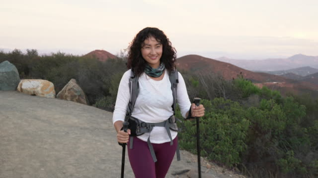 tracking shot young asian woman hiking on mountain - ハイキング点の映像素材/bロール
