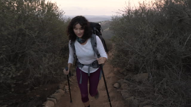 tracking shot young asian woman hiking on mountain - バッグ点の映像素材/bロール