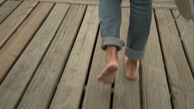vídeos de stock, filmes e b-roll de cu tracking shot young asian woman walking on a dock on a lake - barefoot