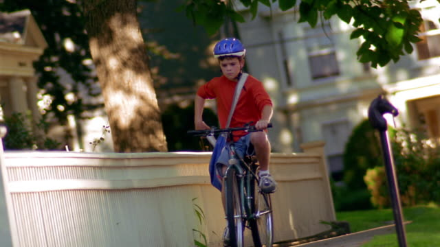 canted tracking shot young boy wearing helmet riding bicycle on sidewalk + delivering newspaper - first job stock videos & royalty-free footage