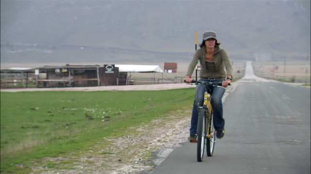 tracking shot young couple riding mountain bikes on road / man speeding up to overtake woman / zoom out to reveal man has fallen in road / woman stopping / another man running towards fallen biker - ausrutscher stock-videos und b-roll-filmmaterial