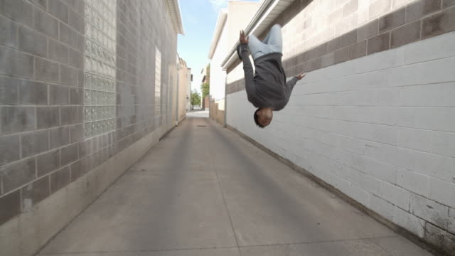 sm tracking shot young man doing parkour in an alley way - バク転点の映像素材/bロール