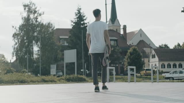 ms tracking shot young man skateboarding in sunny town square - muoversi in una direzione video stock e b–roll
