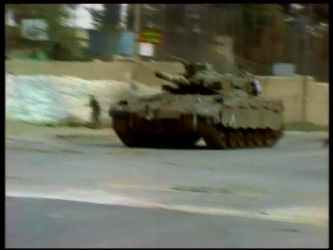 tracking shot young palestinian men and boys throwing stones at israeli tank / jerusalem - 2001 stock videos & royalty-free footage