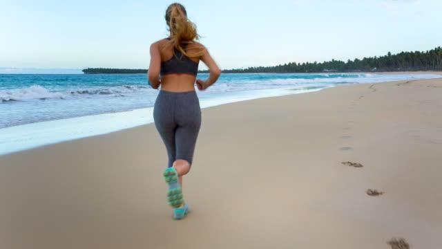 vídeos de stock, filmes e b-roll de ms tracking shot, young woman running along pristine tropical beach - cabelo louro
