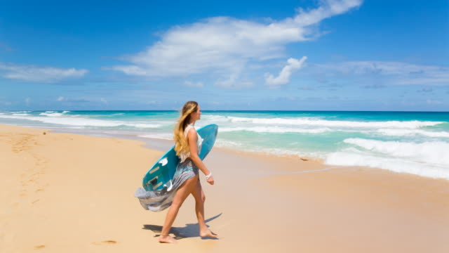 WS tracking shot, young woman walking with surfboard at tropical beach