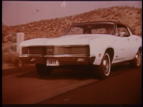 1970 tracking shot zoom in to extreme close up white mercury cyclone? driving on desert road - ford motor company stock videos and b-roll footage