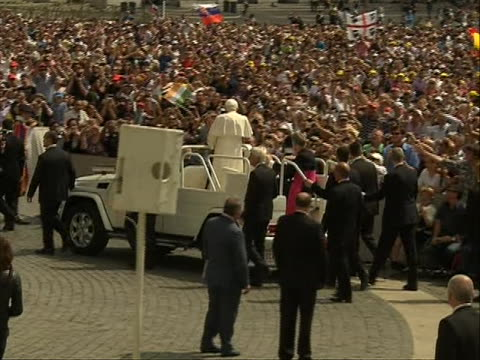 tracking shot zoom-in to mls of popemobile as it drives through the crowd carrying pope benedict xvi. the pope greets the crowd in saint peter's... - ローマ法王専用車点の映像素材/bロール