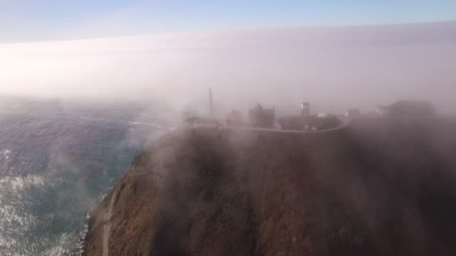 stockvideo's en b-roll-footage met tracking side view of lighthouse on a hill, aerial, 4k, 22s, 3of14, ocean beach, fog, trees, lighthouse crashing waves, reveal, stock video sale - drone discoveries - drone aerial view - sale