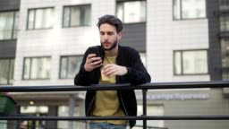 Tracking slow motion shot of handsome young man with beard text messaging on cell phone and drinking coffee leaning on railing in street, from below view