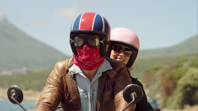 CS tracking  slow motion young couple riding motorbike  to camera